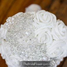 close up view of strip brooch with many silver brooches crystal and pearl on white rose bouquet